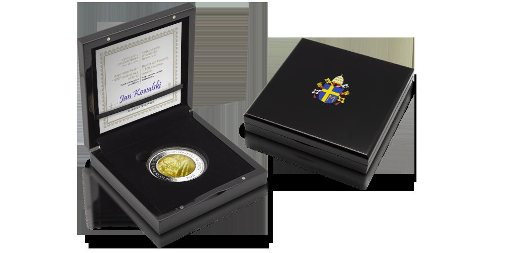Jan Paweł II - srebrna moneta z masą perłową umieszczona w eleganckim pudełku z herbem papieskim na wieczku.